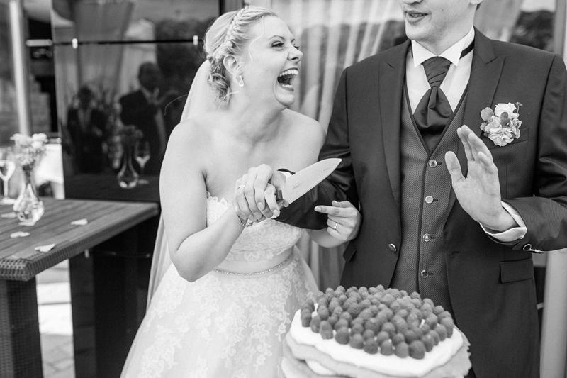 Hochzeitsfoto, schwarzweiß, Brautpaar, Braut, lachen, Tortenanschnitt,