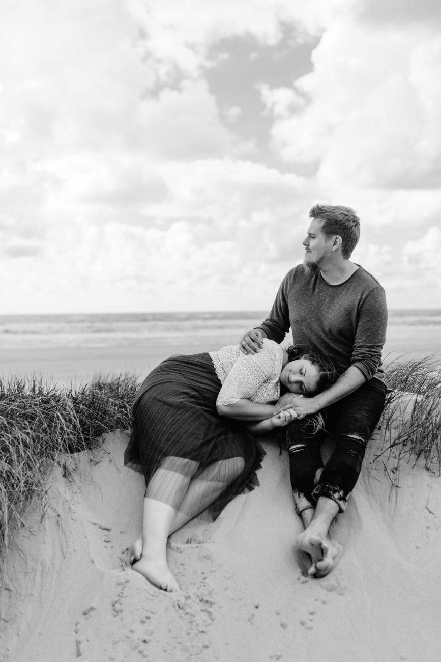 Paar sitzt in den Dünen am Strand, sie kuschelt sich bei ihm an