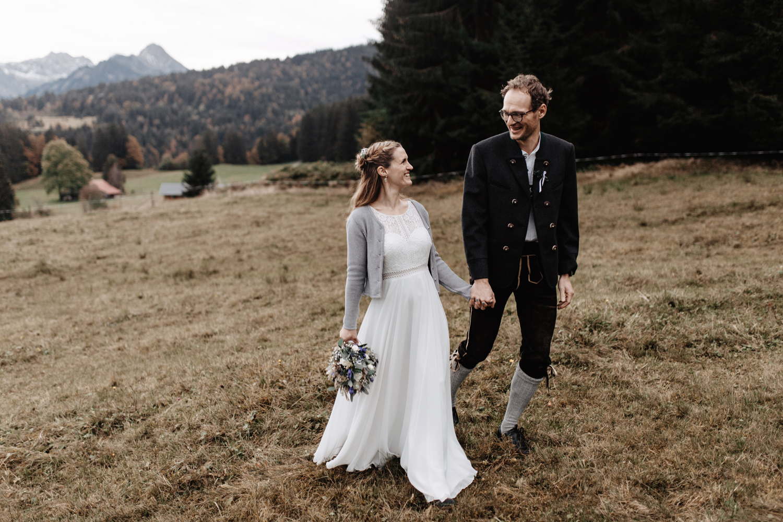 Brautpaar in den Allgäuer Bergen, Hand in Hand auf der Weide vor dem Bergpanorama